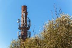 在一个老砖烟囱的电信天线 行业概念 现代技术 输电线在公园 库存照片