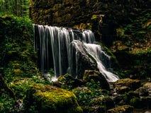 在一个老磨房的废墟的巨大的瀑布在森林里 免版税库存图片