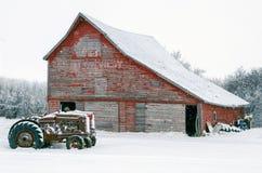 在一个老红色谷仓前面的葡萄酒拖拉机雪的 库存照片