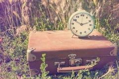 在一个老经典棕色皮革手提箱的葡萄酒闹钟 免版税库存照片