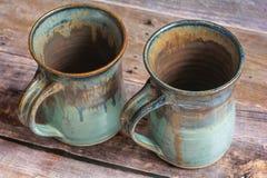 在一个老谷仓板地板上的两个土气黏土杯子 免版税库存图片