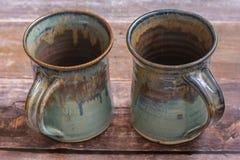 在一个老谷仓板地板上的两个配比的土气黏土杯子 库存图片