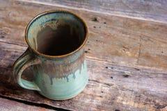 在一个老谷仓板地板上的土气黏土杯子 免版税库存照片