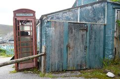 在一个老车库旁边的红色电话亭 库存图片