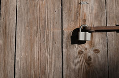 在一个老金属定象的新的铁锁在一个高木门垂悬 库存图片