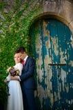 在一个老门的背景的婚礼夫妇 库存照片