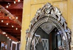 在一个老黄色木门的葡萄酒刻花玻璃威尼斯式镜子 免版税库存照片