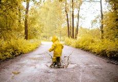在一个肮脏的水坑的小女孩跳跃的乐趣 免版税库存图片