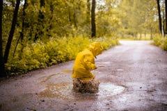 在一个肮脏的水坑的小女孩跳跃的乐趣 库存图片