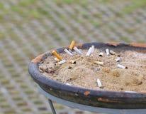 在一个肮脏的烟灰缸的熏制的香烟 免版税库存图片