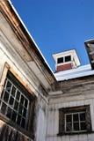 在一个肮脏的白色新英格兰谷仓的明亮的蓝天在一个晴朗的冬日 免版税图库摄影