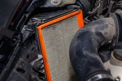 在一个肮脏的空气过滤器的特写镜头有在一辆优质汽车的机舱安装的橙色框架的一个引擎的在期间 库存图片