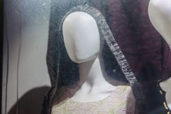 在一个肮脏的窗口后的匿名的时装模特在晚上 库存图片