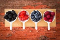 在一个脏的木柜台的新鲜的被分类的莓果 库存照片