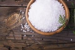 在一个自然木碗的大白海盐有新鲜的迷迭香小树枝的在简单的背景的 选择聚焦 免版税库存图片