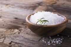 在一个自然木碗的大白海盐有新鲜的迷迭香小树枝的在简单的背景的 选择聚焦 免版税库存照片