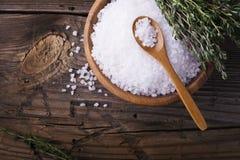 在一个自然木碗的大白海盐有新鲜的迷迭香小树枝的在简单的背景的 选择聚焦 图库摄影