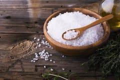 在一个自然木碗的大白海盐有新鲜的迷迭香小树枝的在简单的背景的 选择聚焦 库存图片