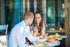 在一个舒适室外咖啡馆的年轻浪漫夫妇在巴黎,法国 免版税库存图片