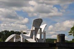 在一个船坞的两把白色阿迪朗达克椅子有完善的云彩的 免版税库存照片