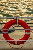 在一个船甲板的橙色救生带在日落期间 免版税库存图片