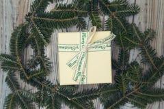 在一个花圈的一个礼物盒在轻的木破旧的背景 免版税库存图片
