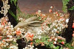 在一个花圈的可爱的兔子雕塑与看花的软的泡影所有在它附近-选择聚焦和关闭  免版税库存照片