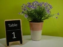 在一个花瓶的小紫色塑料花在与光g的桌上 库存图片