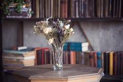 在一个花瓶的干花在图书馆桌上 免版税库存照片