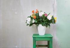 在一个花瓶的庭院玫瑰在一把木土气凳子 免版税库存照片