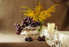在一个花瓶的成熟葡萄在一朵美丽的餐巾和黄色花 免版税库存照片