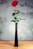 在一个花瓶的红色玫瑰在老桌上 库存图片