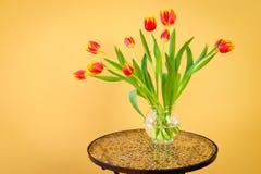 在一个花瓶的红色郁金香在马赛克桌。 免版税库存图片
