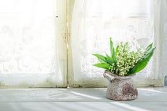 在一个花瓶的铃兰在一个晴朗的窗口附近 免版税库存图片