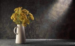 在一个花瓶的黄色花在与剧烈的光的黑暗的背景 免版税图库摄影