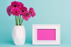 在一个花瓶的黑暗的桃红色大丁草在与空的画框贺卡的一张桌上 愉快的母亲` s天,妇女` s天或生日 库存照片