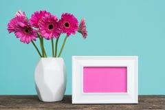 在一个花瓶的黑暗的桃红色大丁草在与空的画框贺卡的一张桌上 库存图片