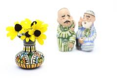 在一个花瓶的黄金菊有陶瓷玩偶的 库存照片