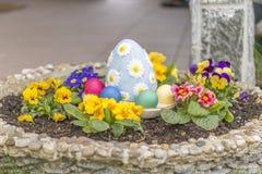 在一个花盆的五颜六色的复活节彩蛋有有角的紫罗兰的开花 免版税库存图片
