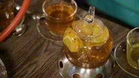在一个茶壶和杯子的热的可口果子茶在一张木桌上 股票录像
