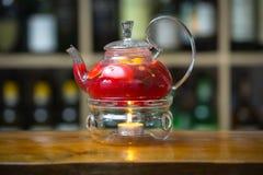 在一个茶壶的红色茶在与一个蜡烛的一个立场在木酒吧柜台 在有瓶的背景机架上 库存照片