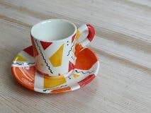 在一个茶碟的小五颜六色的咖啡杯在桌上 库存图片