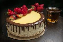 在一个茶碟的草莓在木standDecorated草莓乳酪蛋糕的背景与一杯茶的和草莓 免版税图库摄影