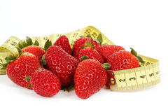 在一个草莓附近的评定的磁带作为饮食的符号 免版税图库摄影