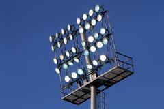 在一个蓝天背景的体育场光 免版税库存图片