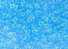 在一个蓝色冬天背景的白色心脏背景。爱textu 库存照片