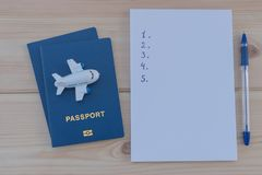 在一个蓝色护照和白色笔记本顶部的小玩具飞机 免版税库存图片