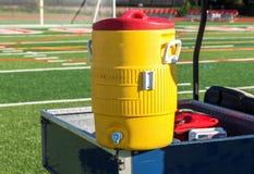 在一个蓝色推车的黄色冷却器有足球网的在背景中 库存图片