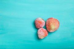 在一个蓝色木切板的冷冻草莓 有选择性的fo 免版税库存照片
