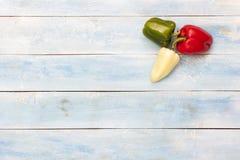 在一个蓝色木板的五颜六色的新鲜的胡椒 库存照片